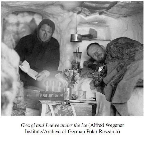 Picture of two members of Wegner's team in their underground winter home. Neither of them are smiling, one is looking up from reading a book. the other is on his ice bed under blankets.